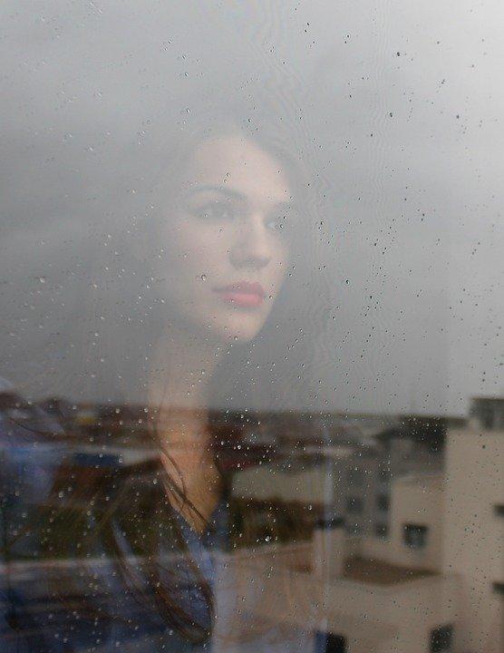 Regen en gedachten van weemoed. Kijkend voor het raam naar de regendruppels.